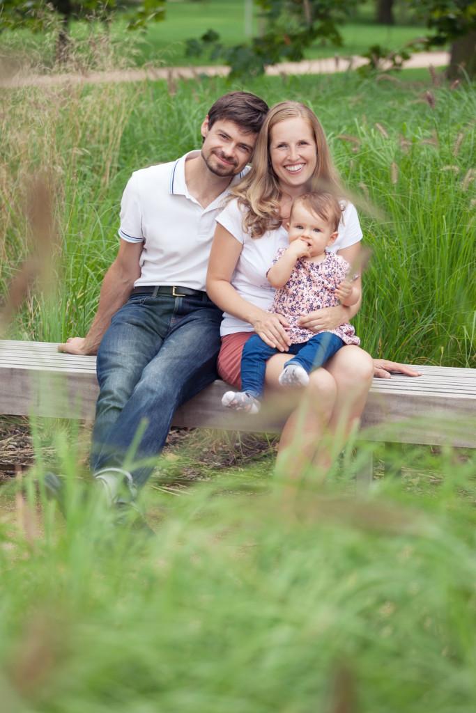 Rodina sedí na lavičce, dcera sedí na klíně maminky