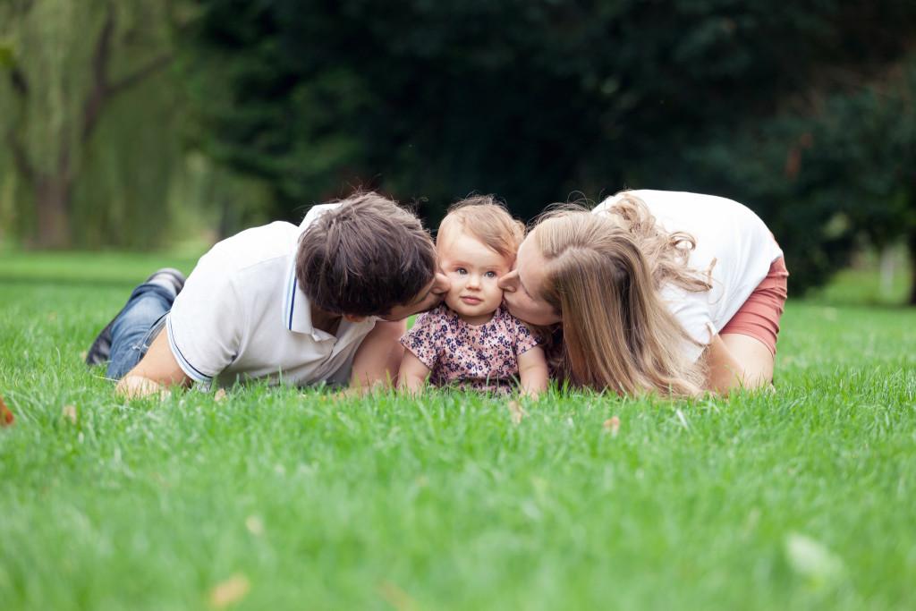 Rodiče dávají dceři pusu na tvář