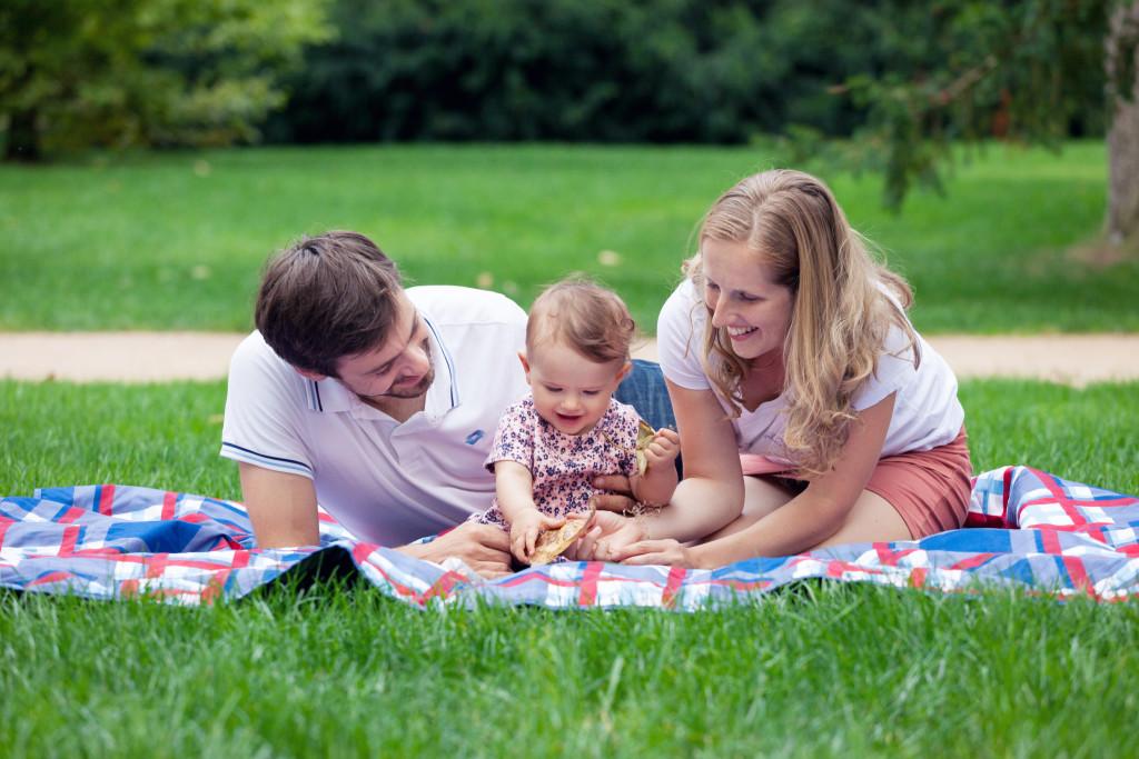 Rodiče s dcerou sedí na dece, úsměv, hraní