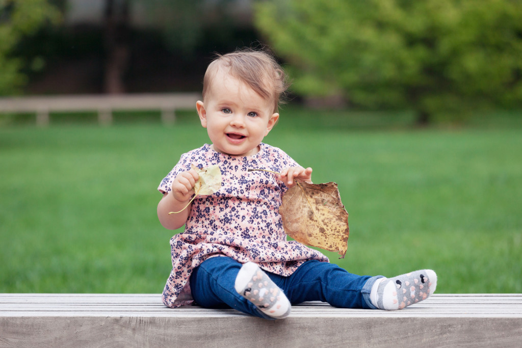 Holčička sedí na lavičce a drží listy