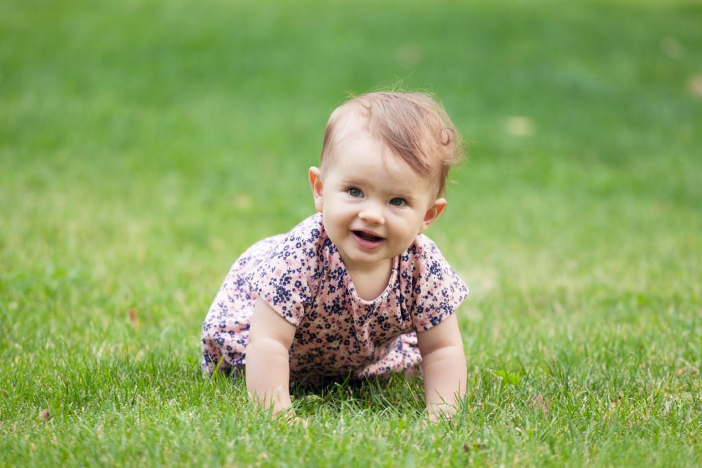 Portrét holčičky lezoucí v trávě