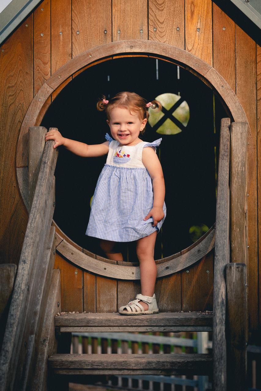 Malá holčička kouká z dětského domečku