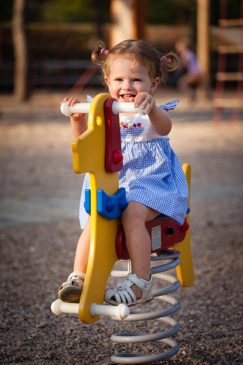 Malá holčička se houpe na dětské houpačce
