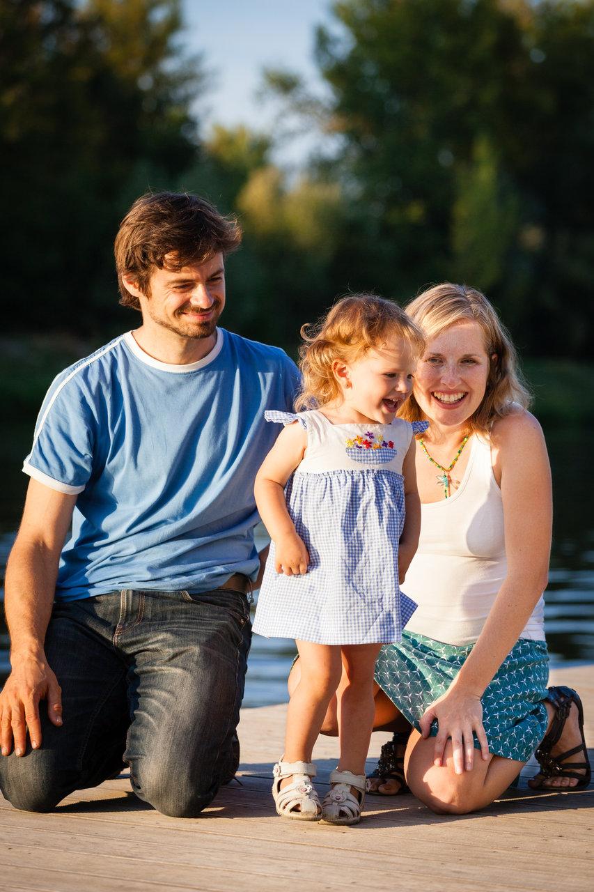 Tatínek s maminkou klečí, dcera kouká do vody a směje se