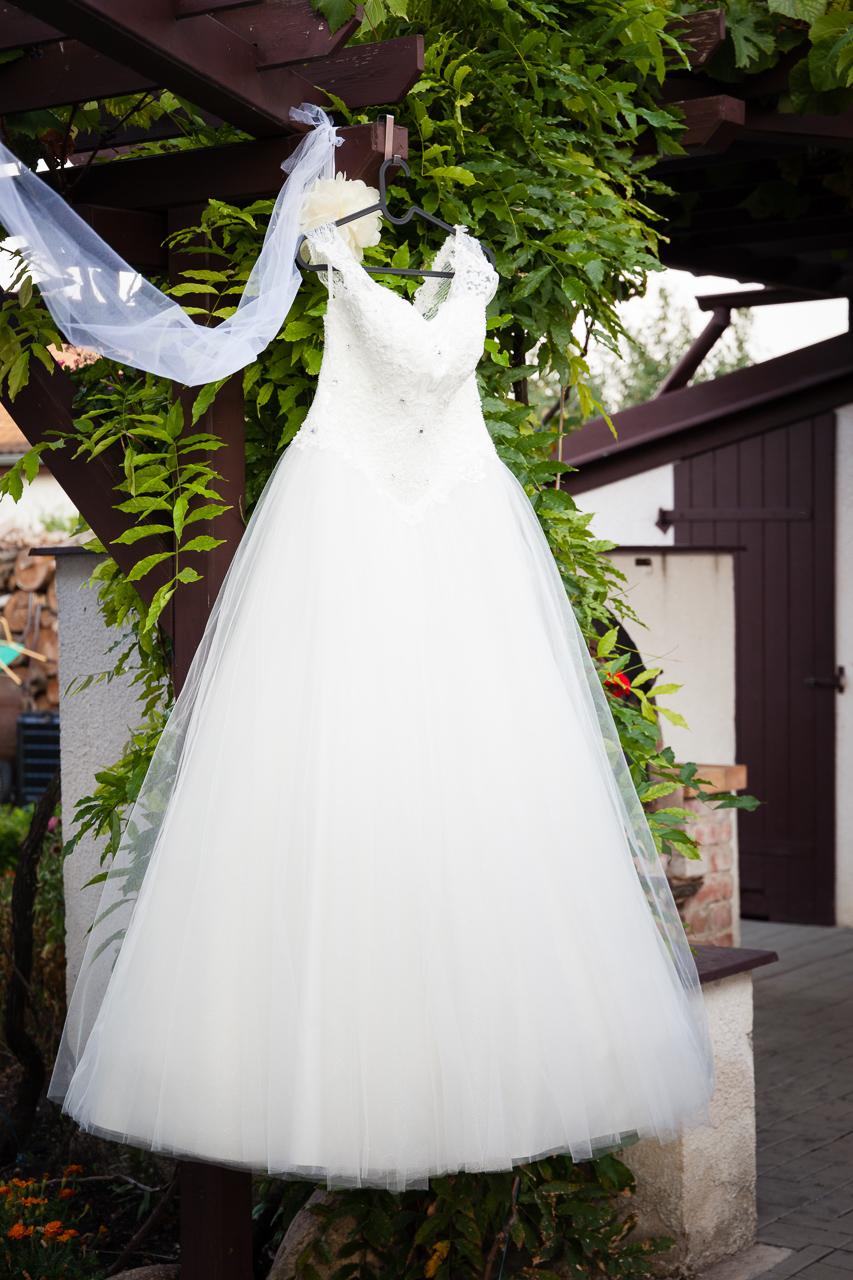 Šaty nevěsty visící na ramínku v pergole