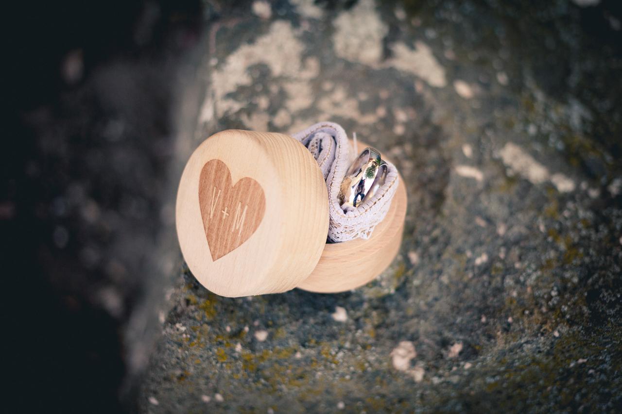 Detail svatebních prstýnků v dřevěné krabičce na kameni