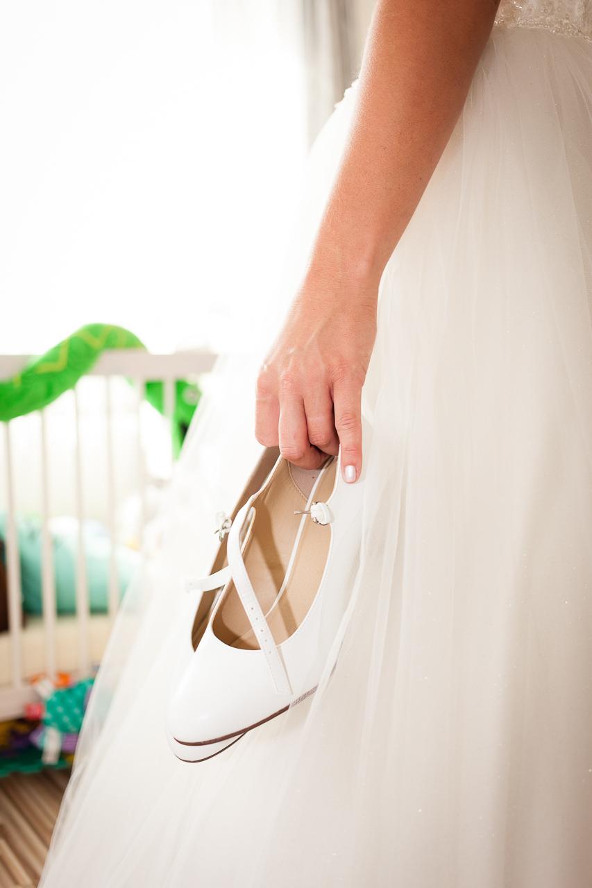 Detail, nevěsta drží lodičky v levé ruce