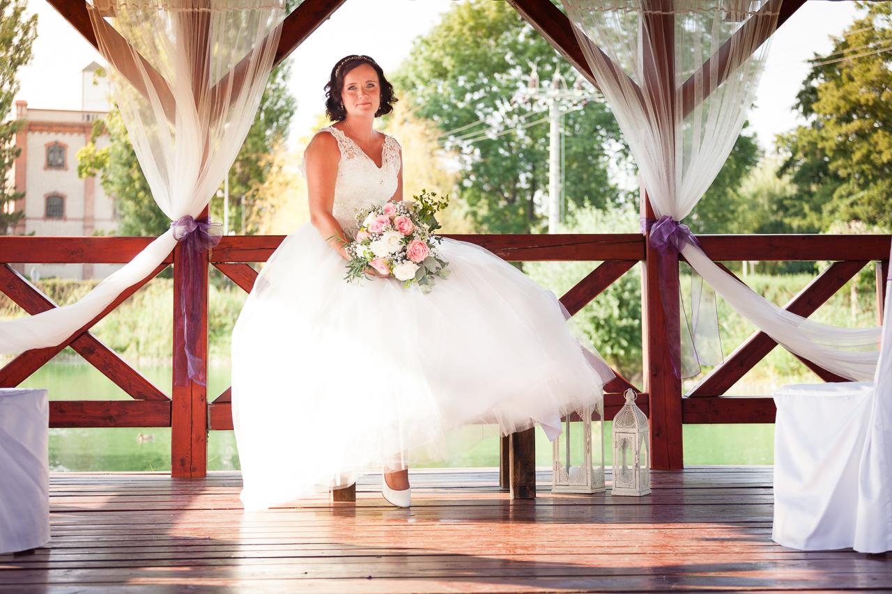 Nevěsta sedí v altánku na stole a má kytici v ruce