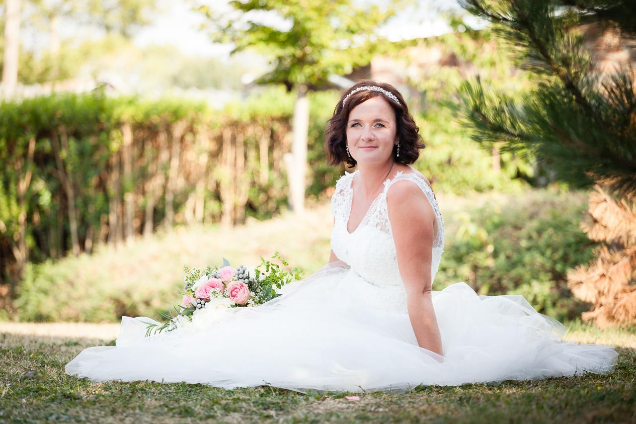 Portrét nevěsty sedící s kyticí na trávě