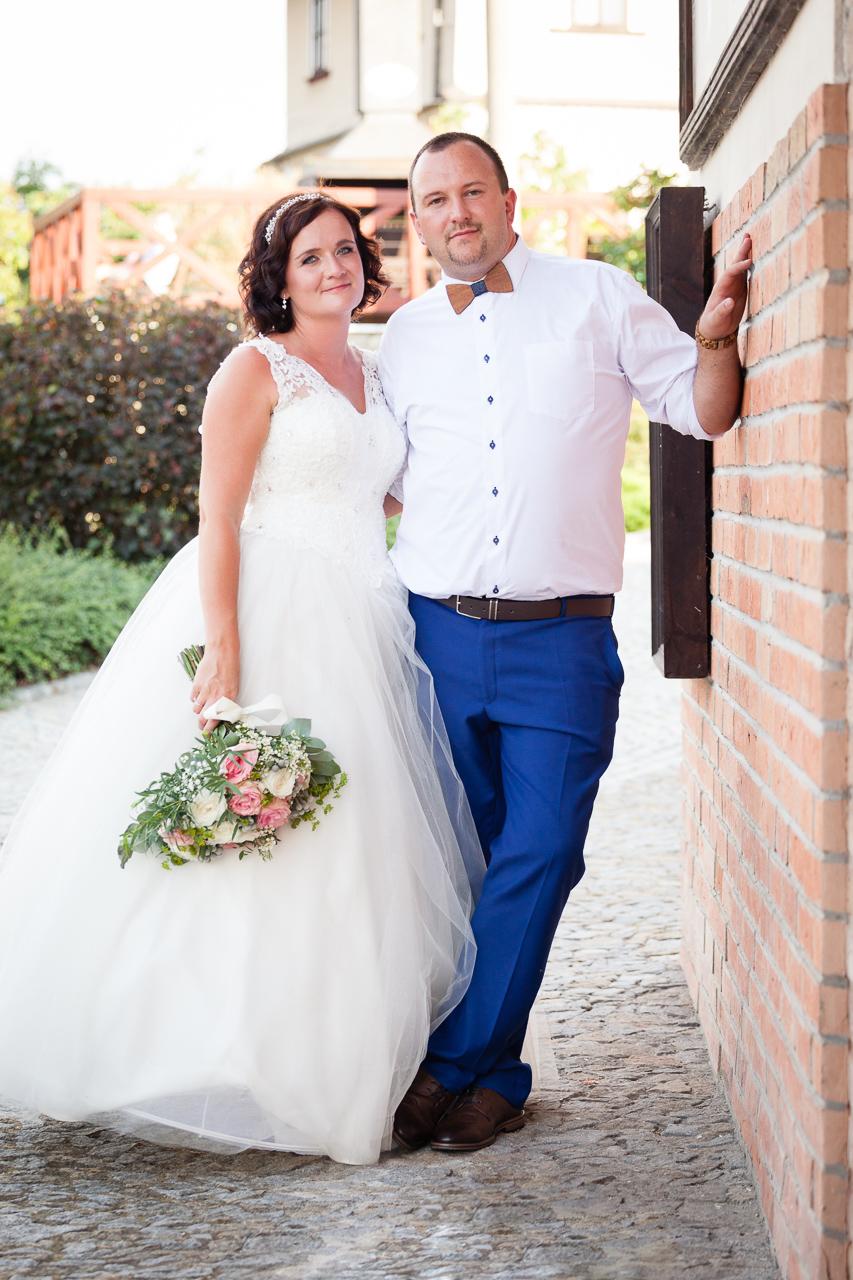 Nevěsta se ženichem stojí u zdi, uvolněně