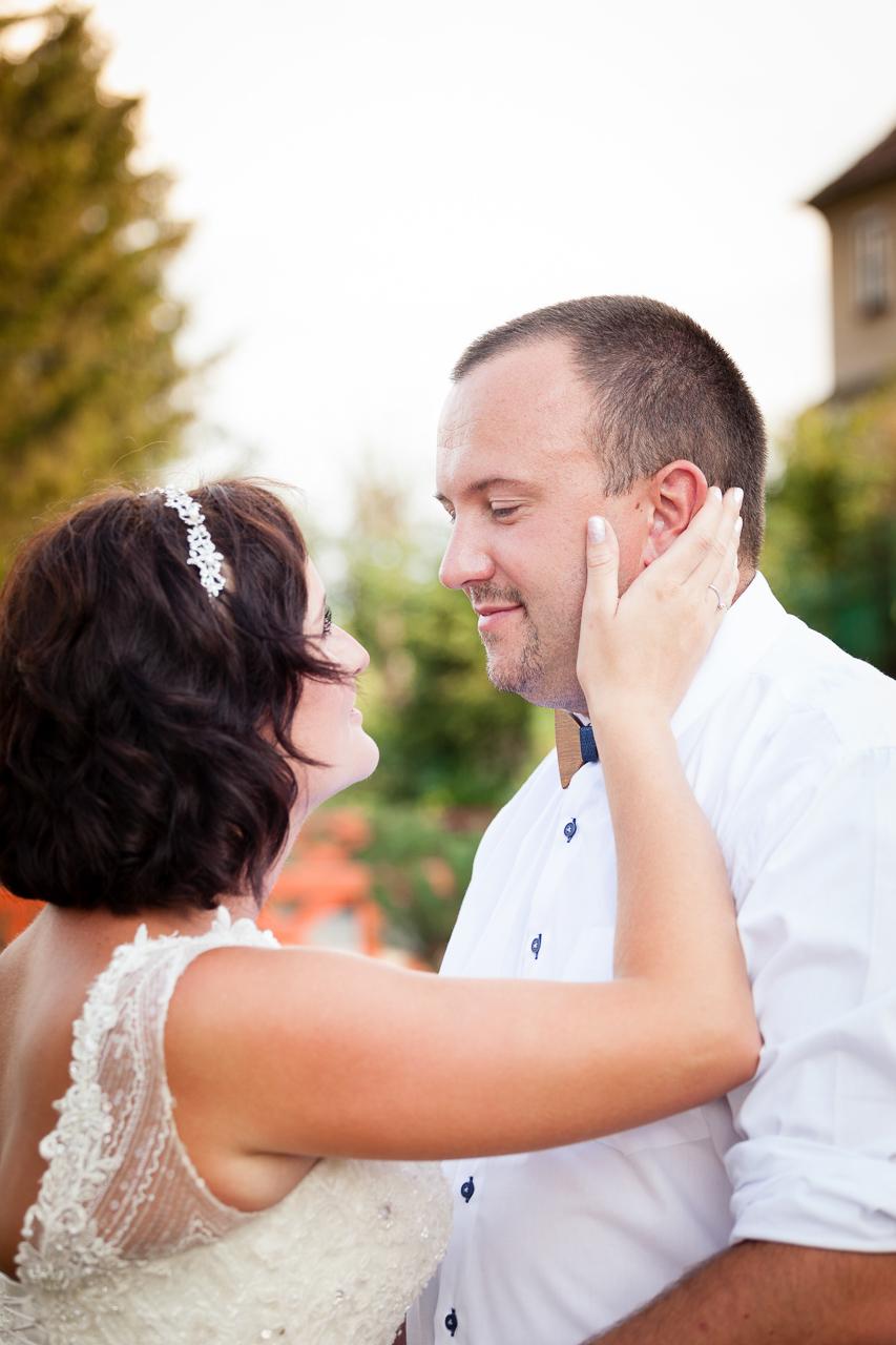 Nevěsta hladí ženicha po tváři, detail