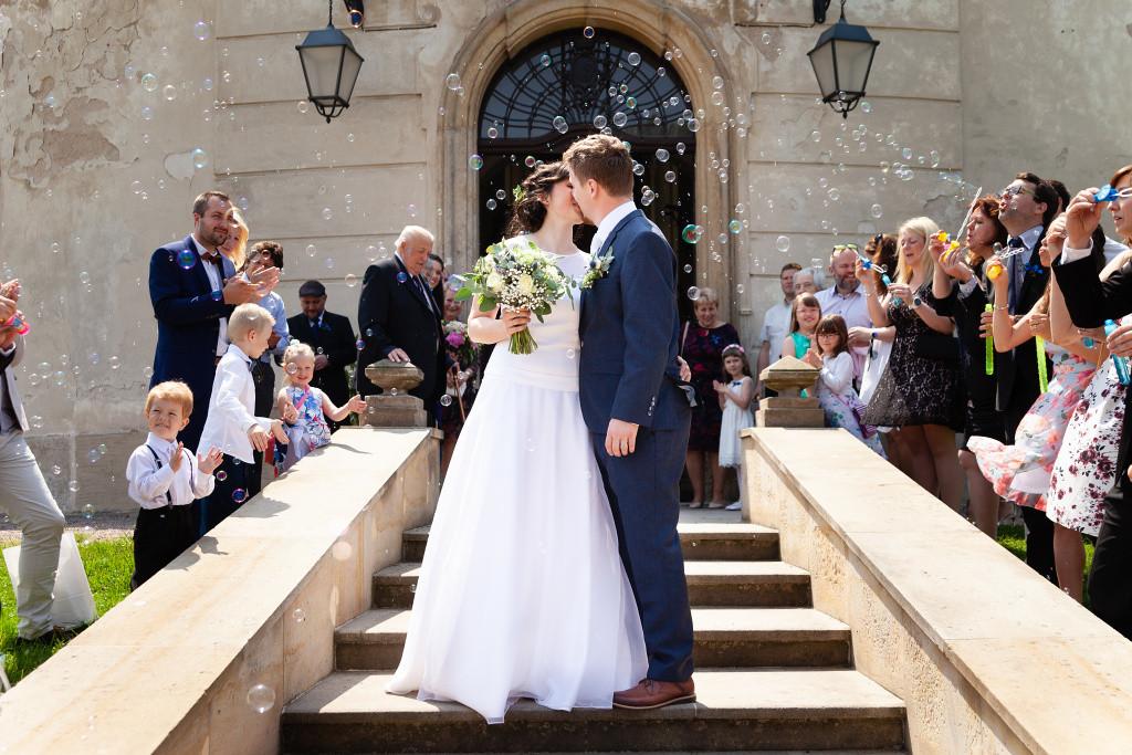 Nevěsta se ženichem si dívají polibek před zámkem Karlova Koruna