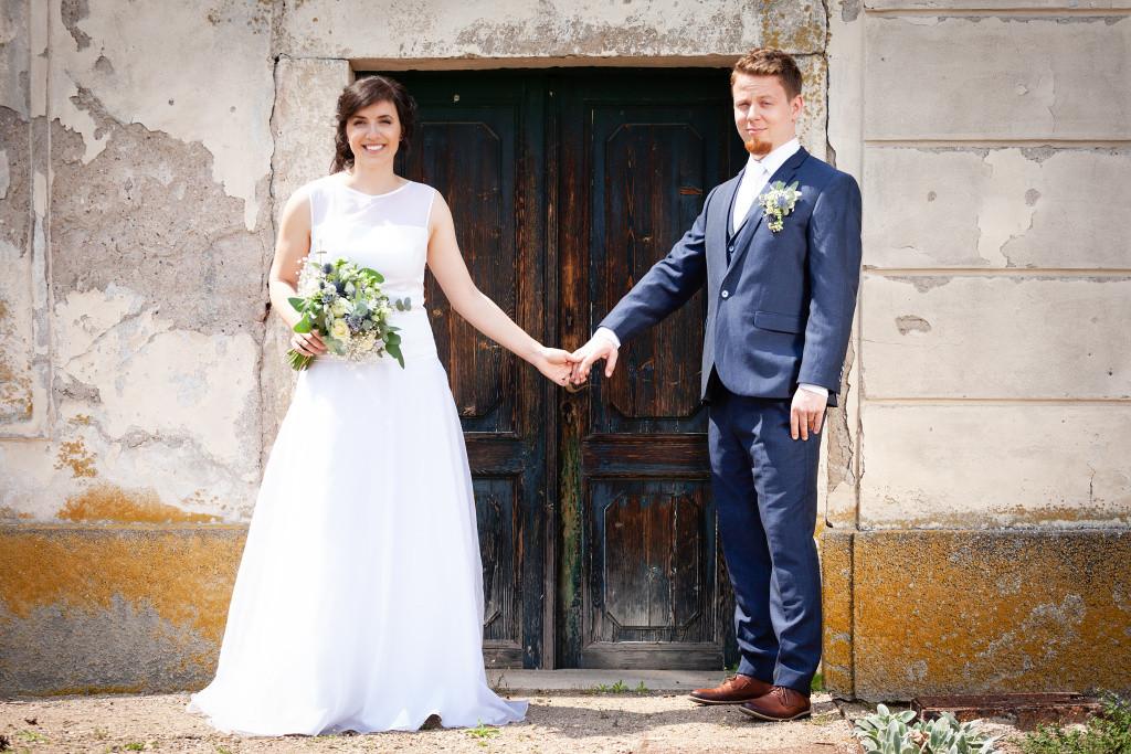 Nevěsta se drží za ruce se ženichem přede dveřmi, Karlova Koruna
