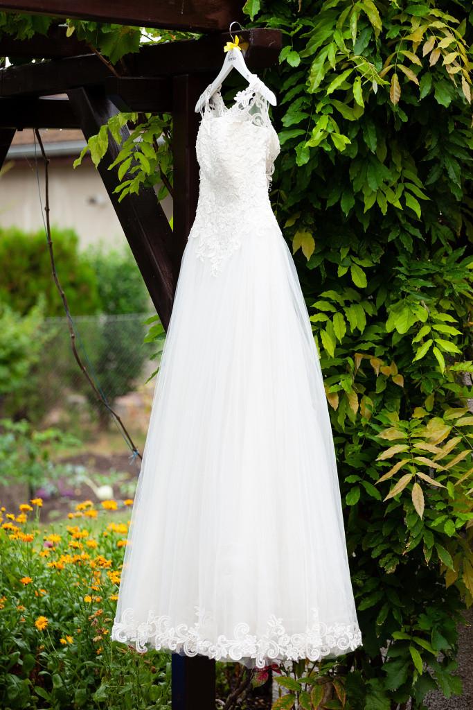 Šaty nevěsty visí na pergole