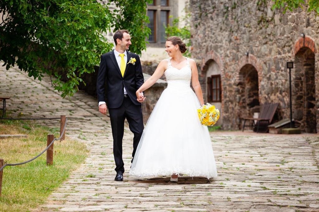 Nevěsta se ženichem jdou po nádvoří