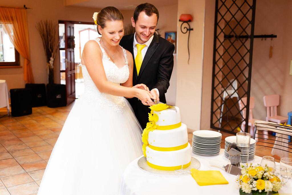 Nevěsta se ženichem zakrojují dort