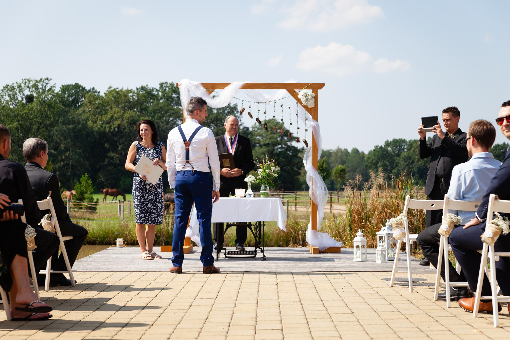 Ženich čeká na nevěstu u obřadního stolu