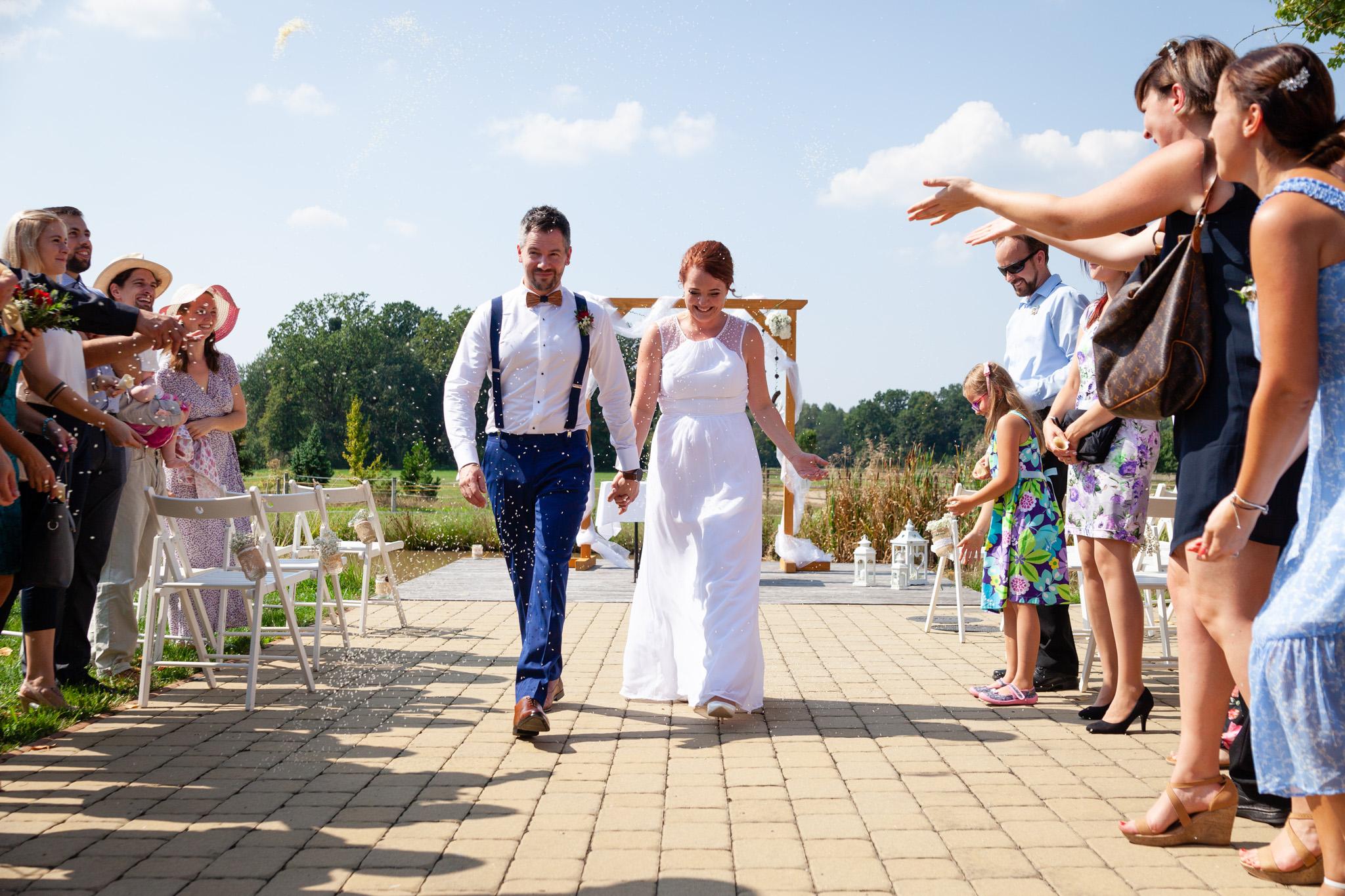 Nevěsta a ženich prochází špalírem, který na ně hází rýži