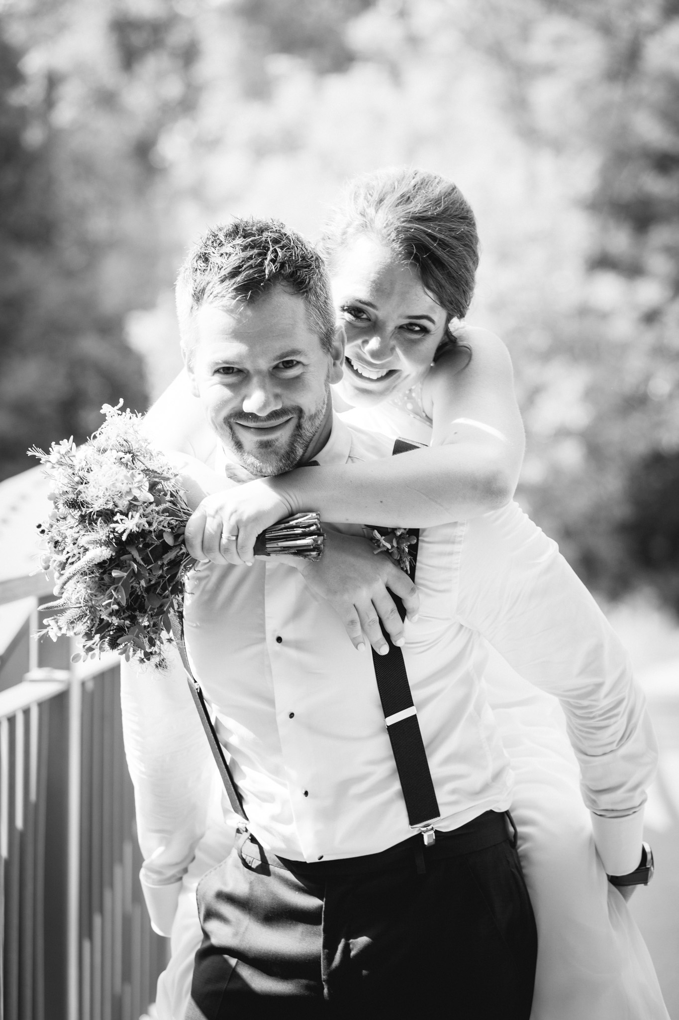 Ženich nese nevěstu na zádech, svatební portrét