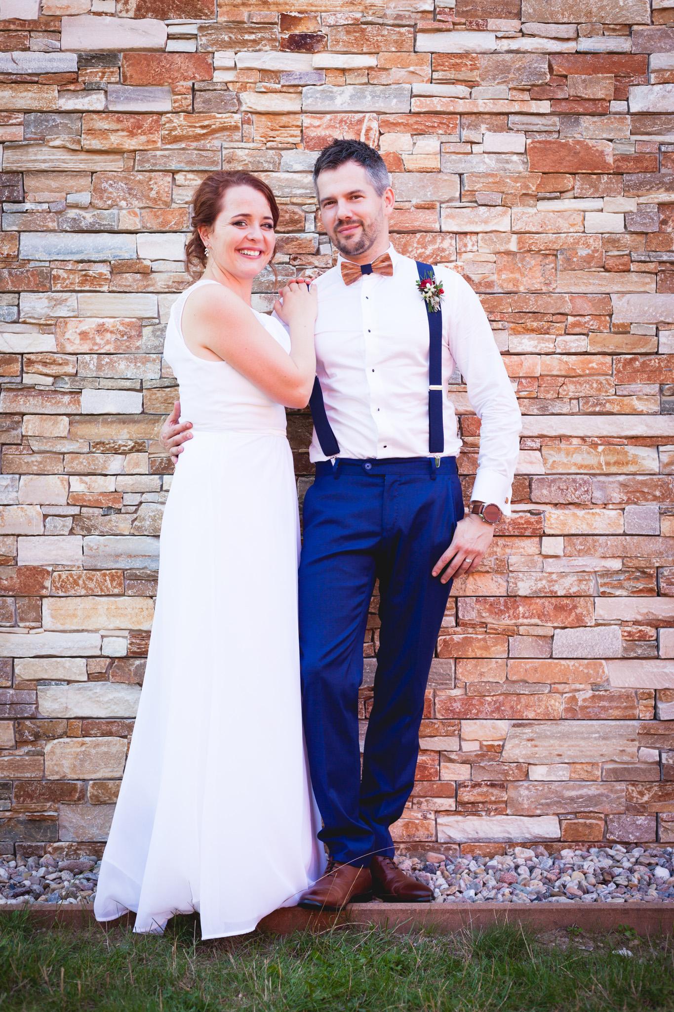 Svatební portrét nevěsty a ženicha u zdi