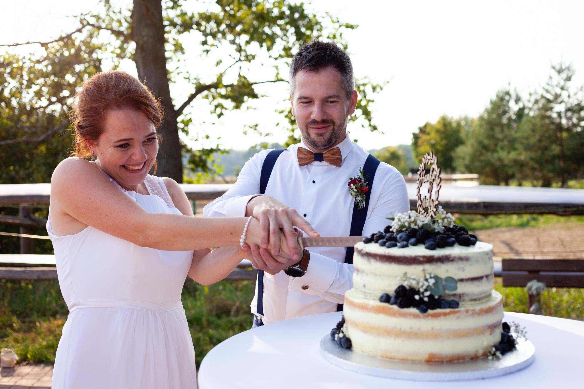 Nevěsta a ženich zařezávají dort