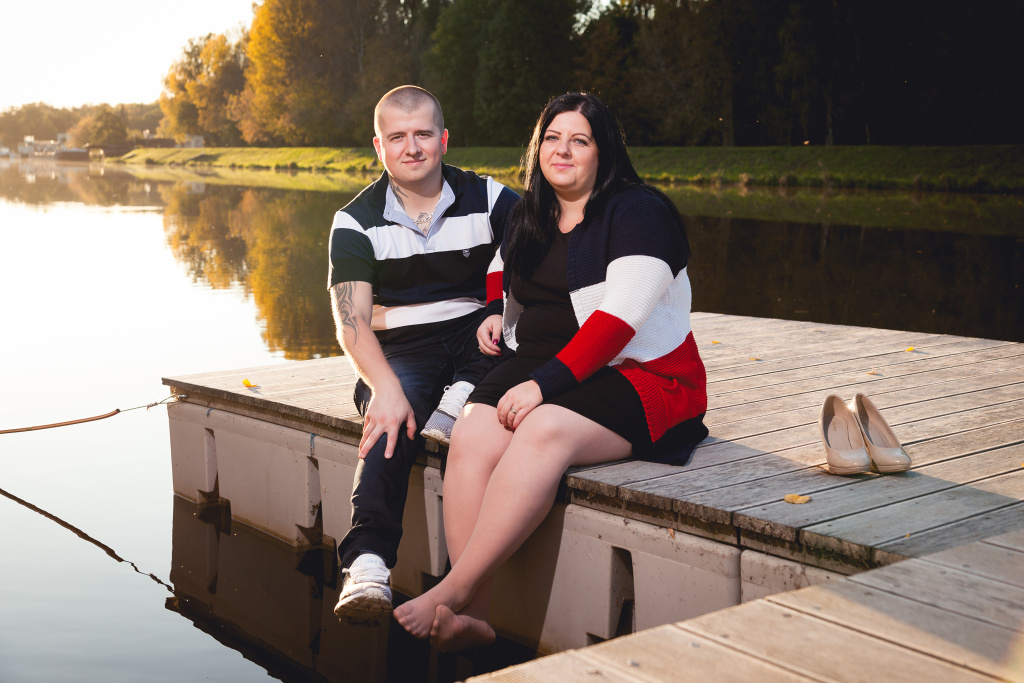 Manželé sedí na mole při západu slunce