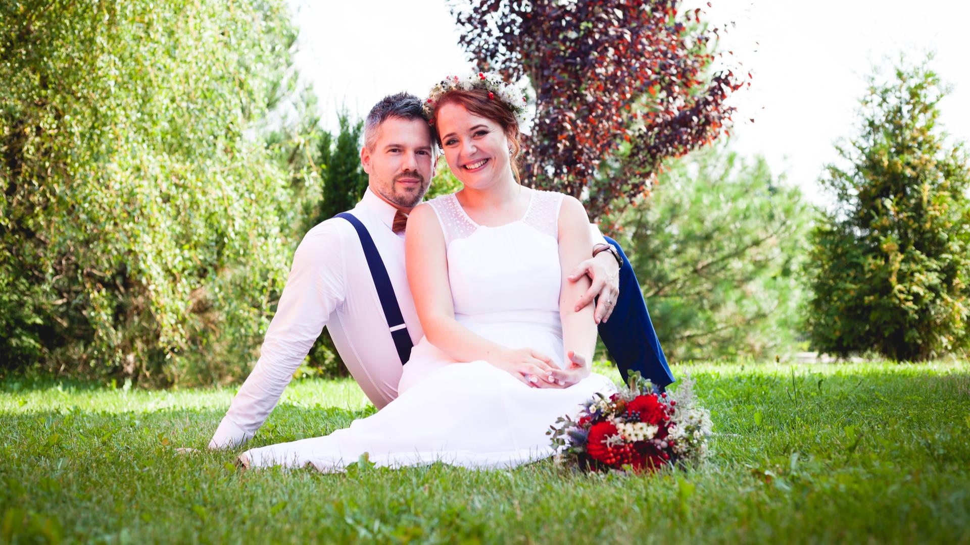 Svatební portrét, nevěsta a ženich sedí v trávě
