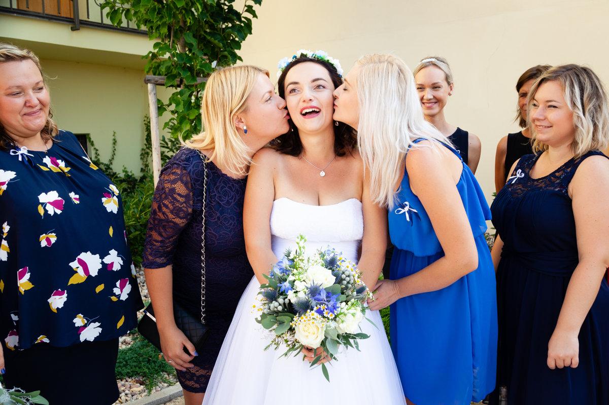 Nevěsta dostává pusu od kamarádek