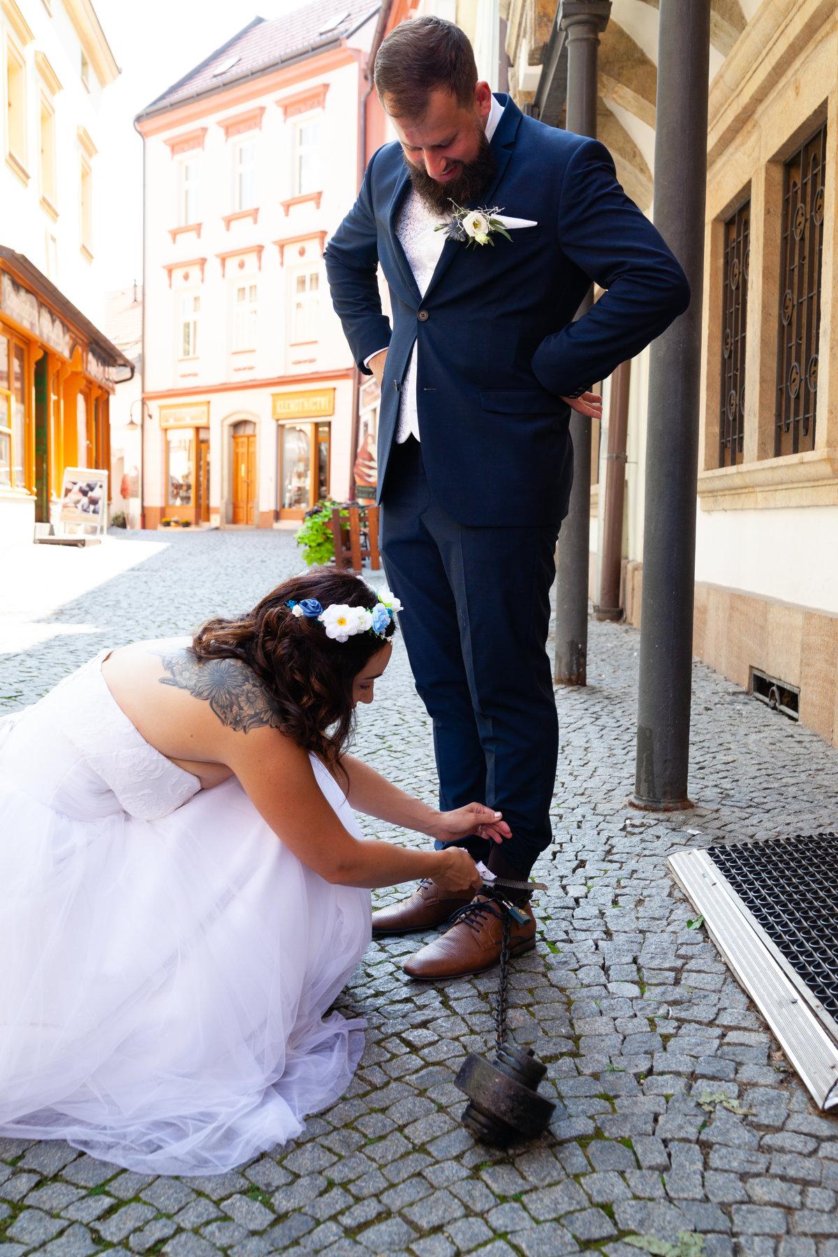 Nevěsta se snaží ženichovi odstranit kouli na noze