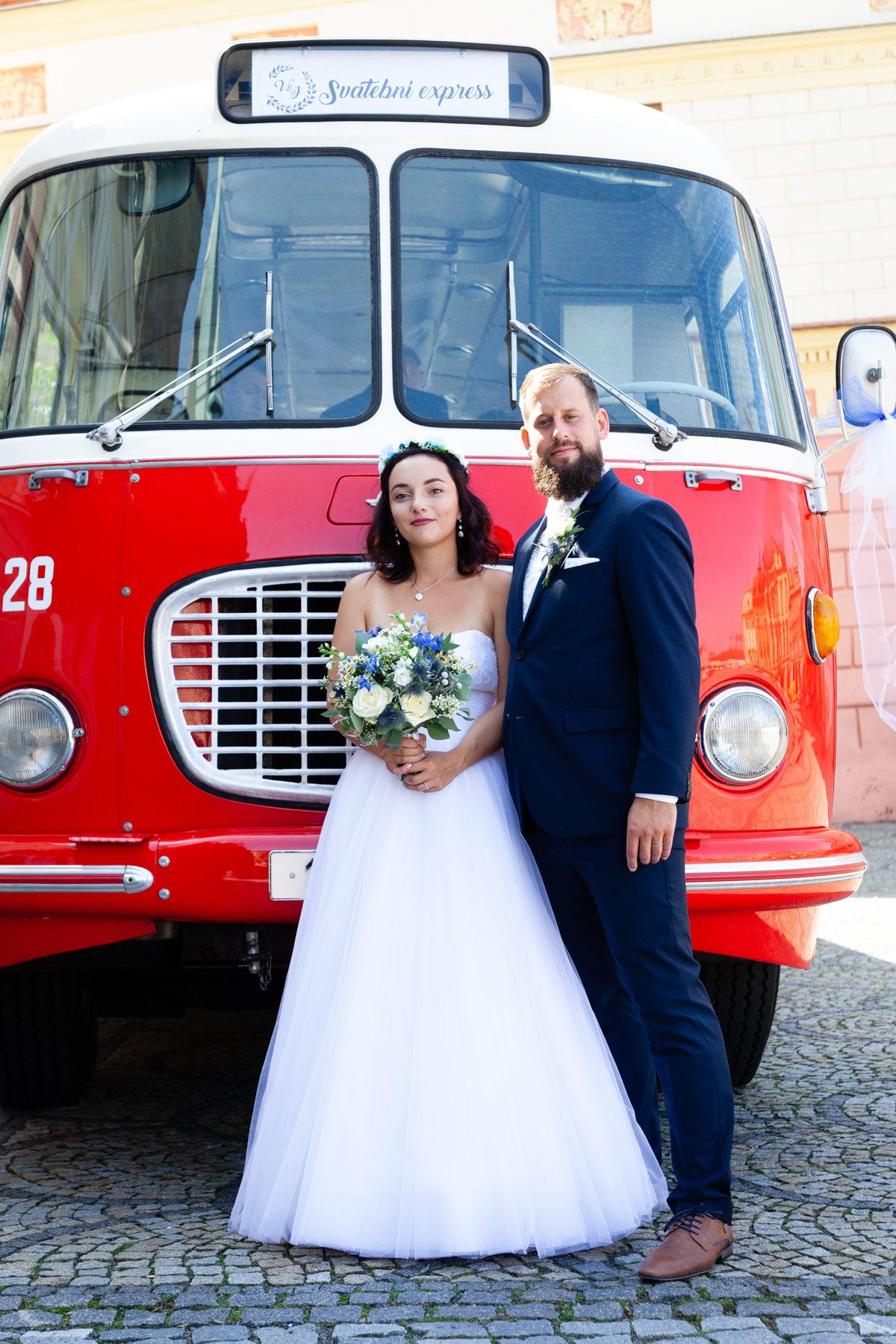 Nevěsta a ženich stojící u autobusu