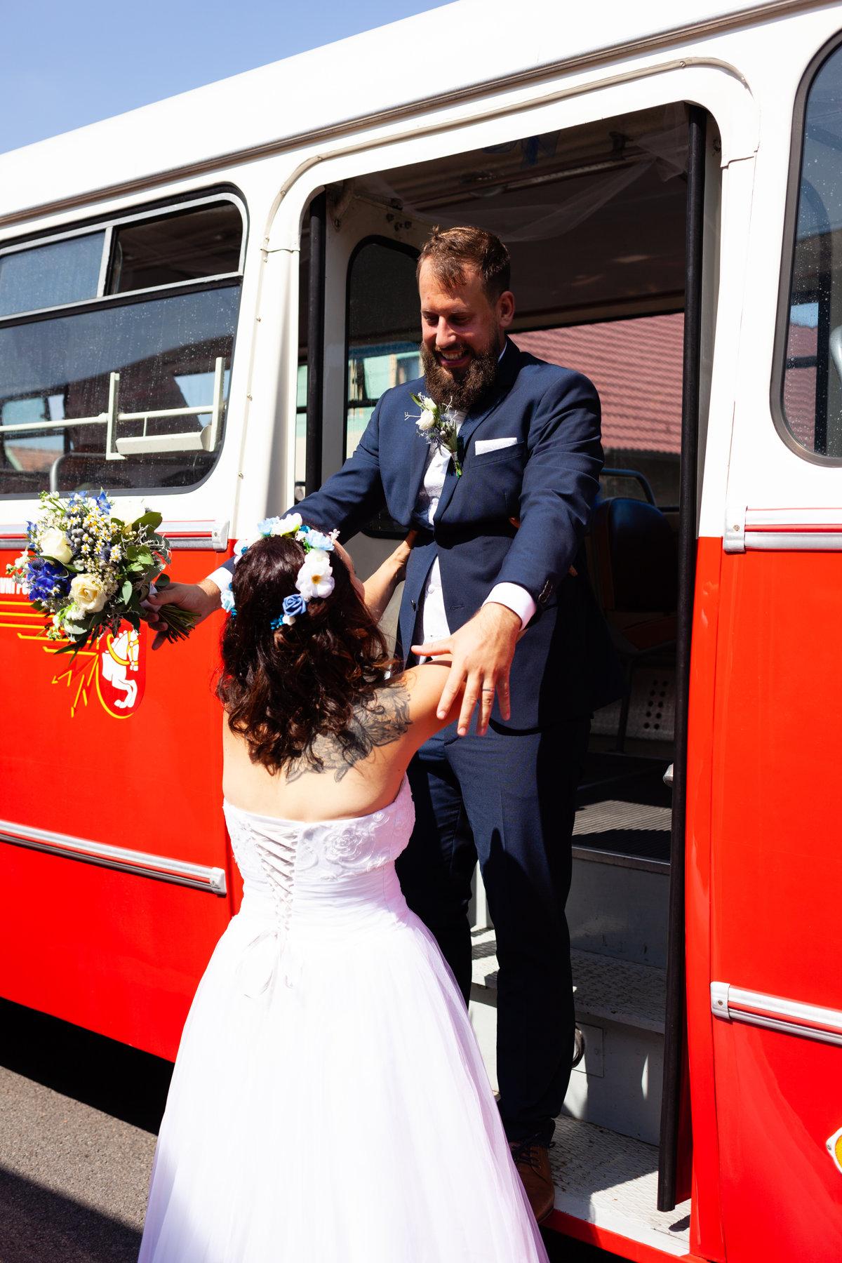Nevěsta pomáhá ženichovi ze svatebního autobusu