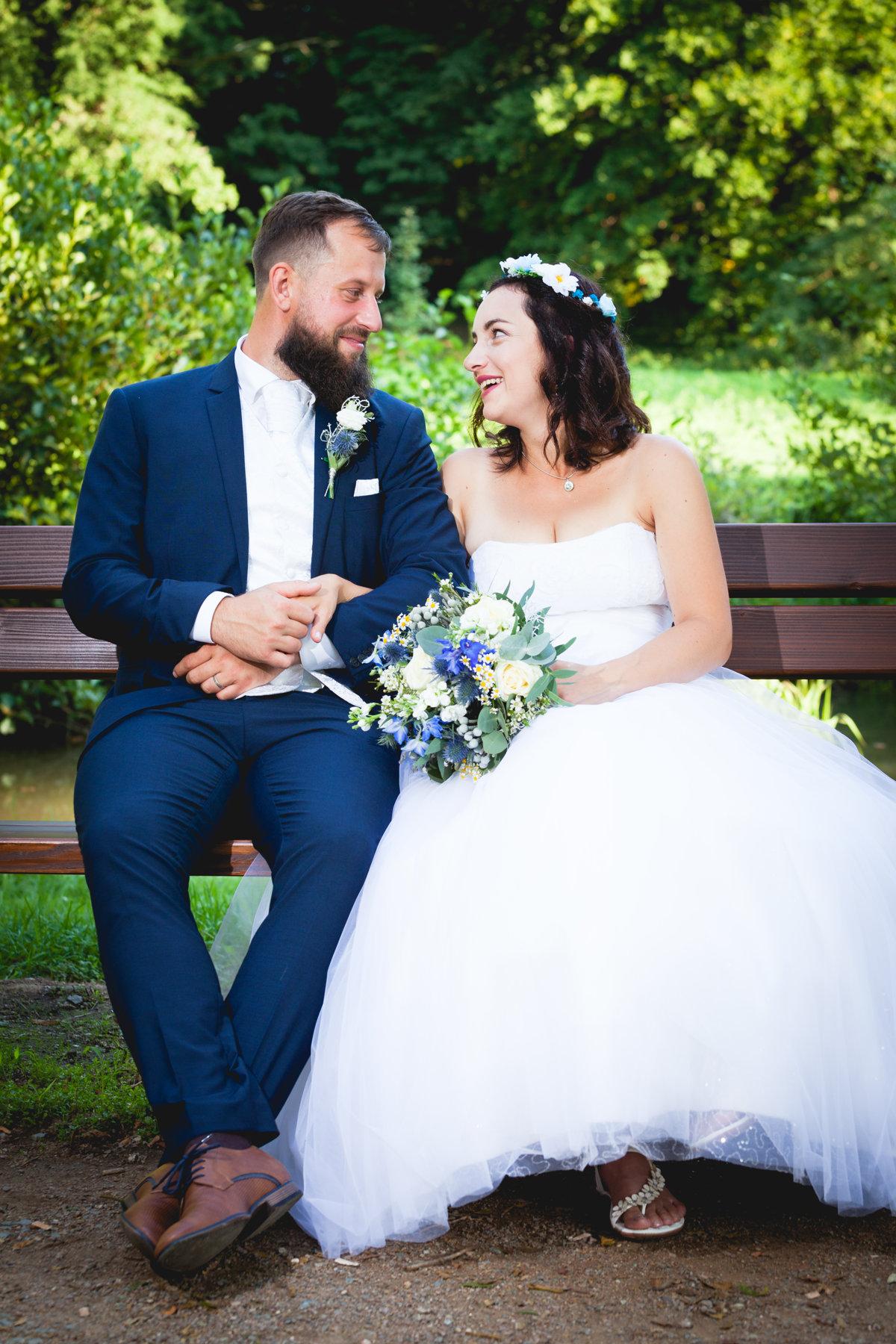 Svatební portrét, nevěsta se ženichem sedí na lavičce a dívají se na sebe