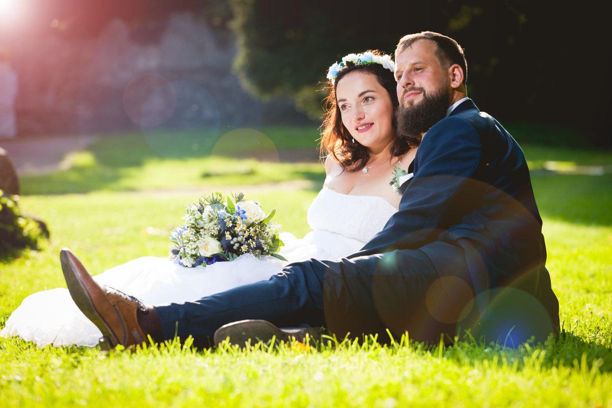 Nevěsta se ženichem sedí spolu v trávě, zámek Choltice