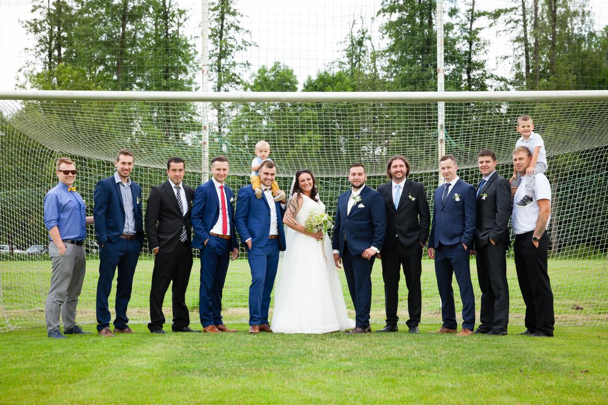 Portrét nevěsty a ženicha s kamarády ve fotbalové brance