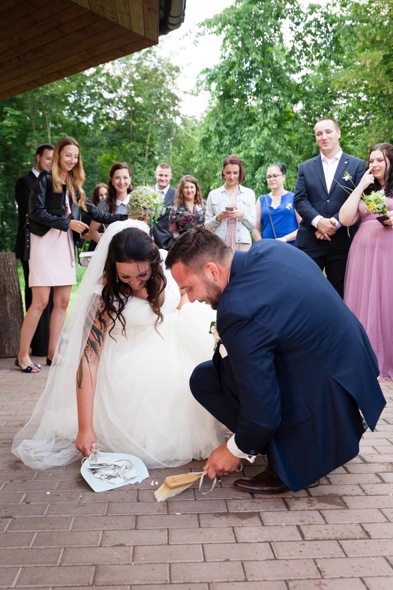 Nevěsta se ženichem zametají střepy