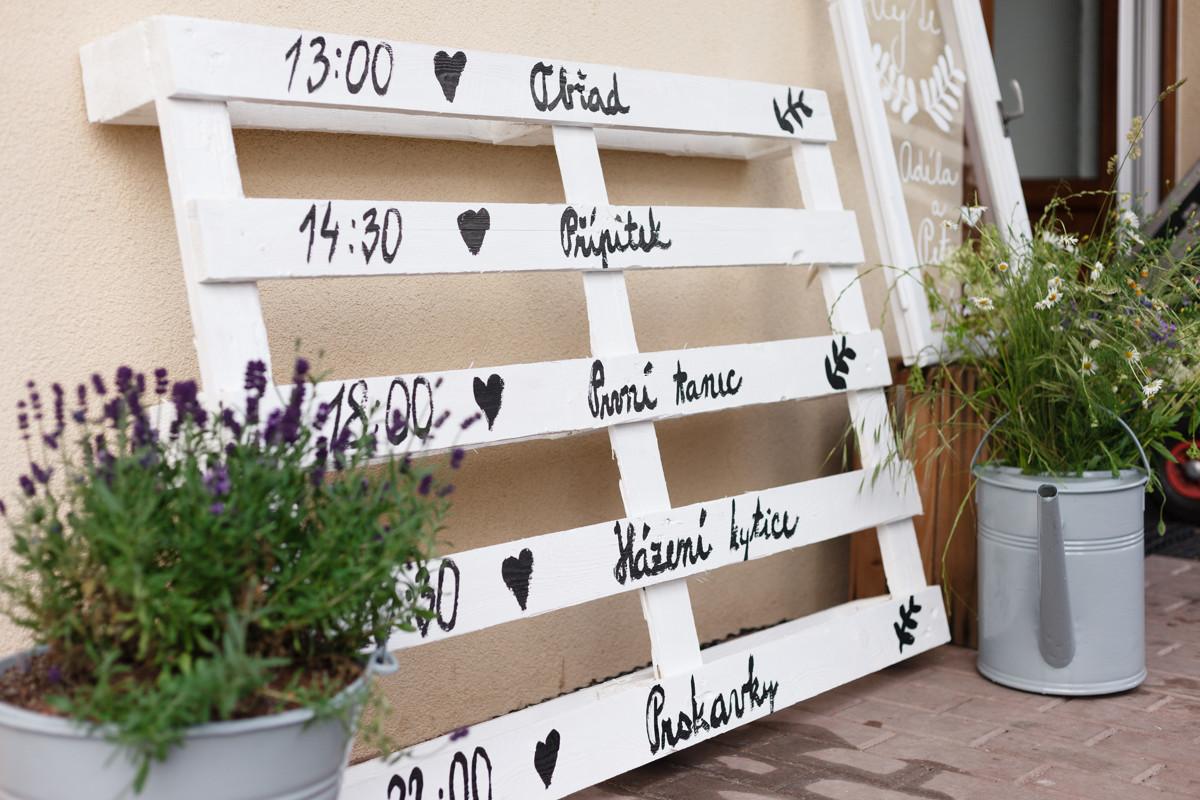 Detail na dřevěnou paletu se svatebním programem