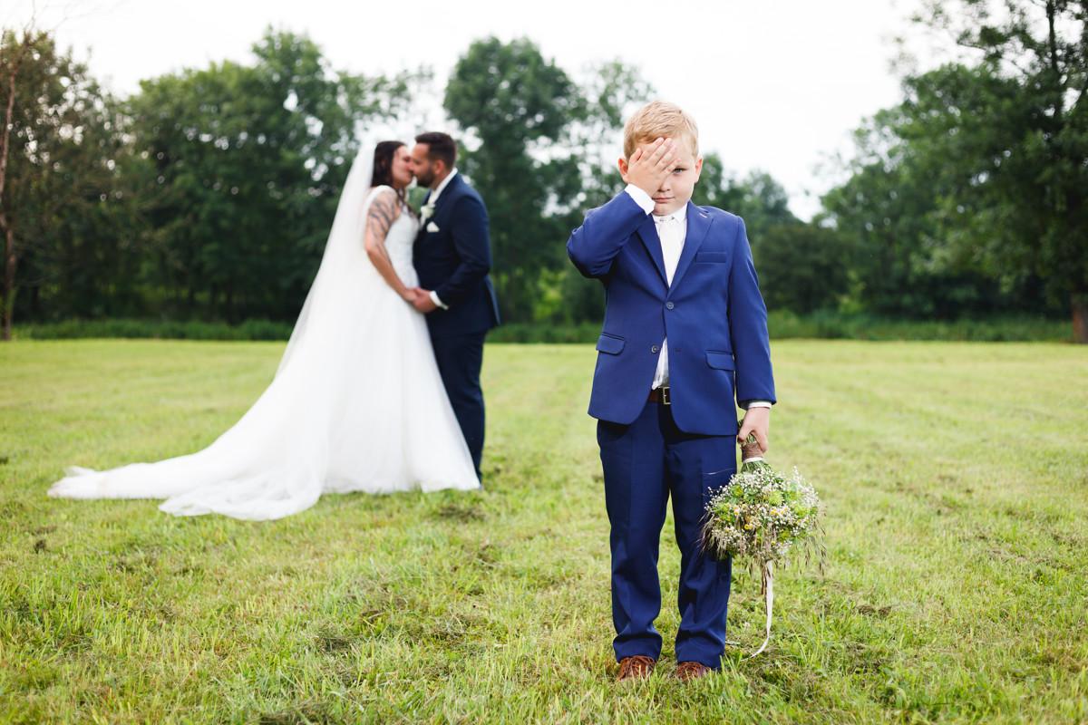 Svatební portrét, syn kouká do kamery, rodiče se líbají