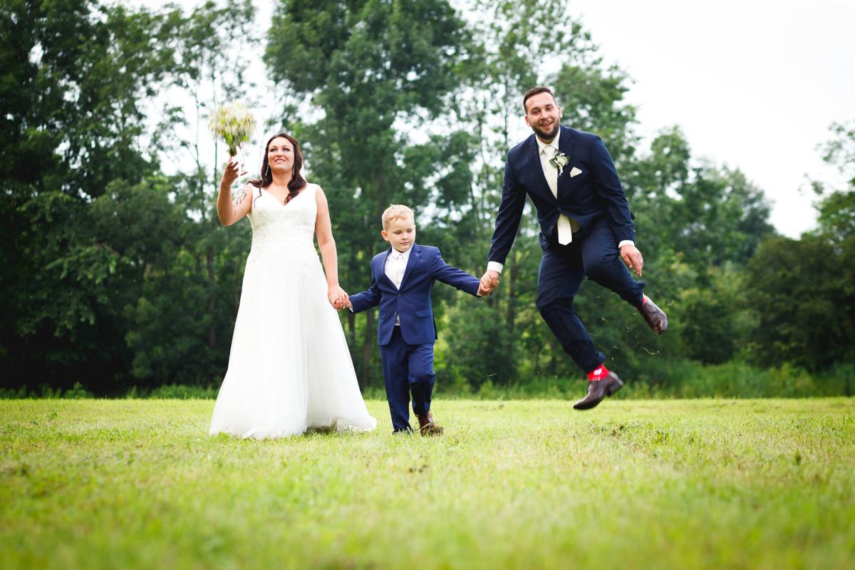 Novomanželé se synem jdou po louce