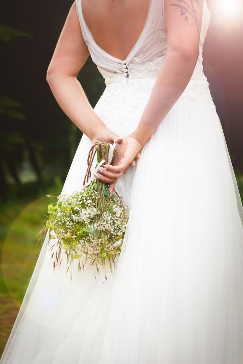 Nevěsta drží kytici za zády