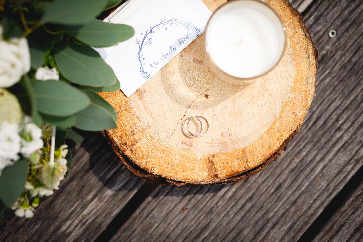 Detail prstýnků a svatební kytice, svíčka, dřevo, svatba