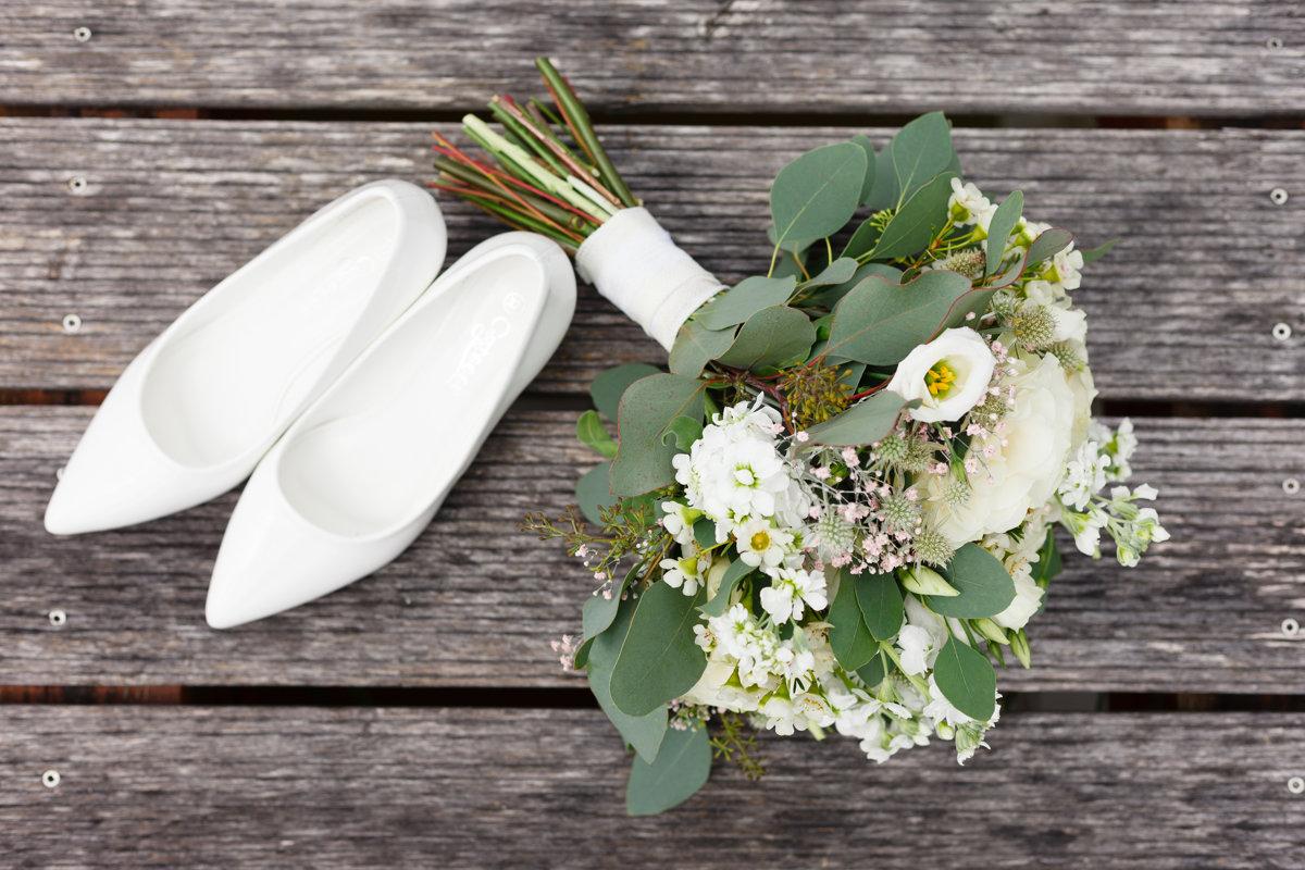 Detail na svatební kytici a boty nevěsty