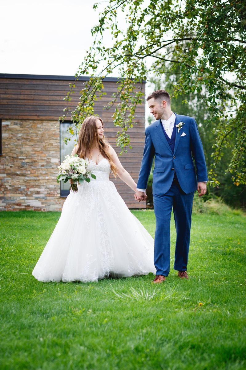 Svatební portrét, nevěsta se ženichem se prochází po trávě