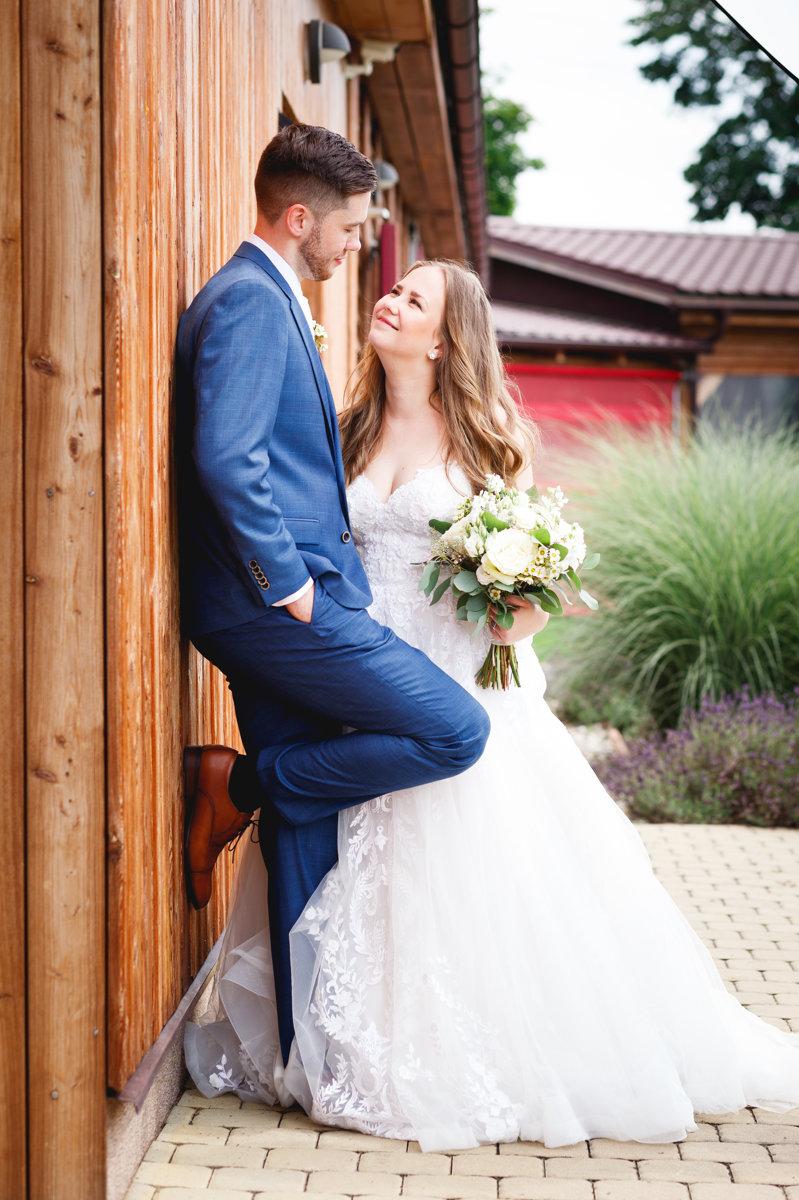 Svatební portrét, ženich se opírá o dřevěnou zeď a nevěsta se na něho dívá