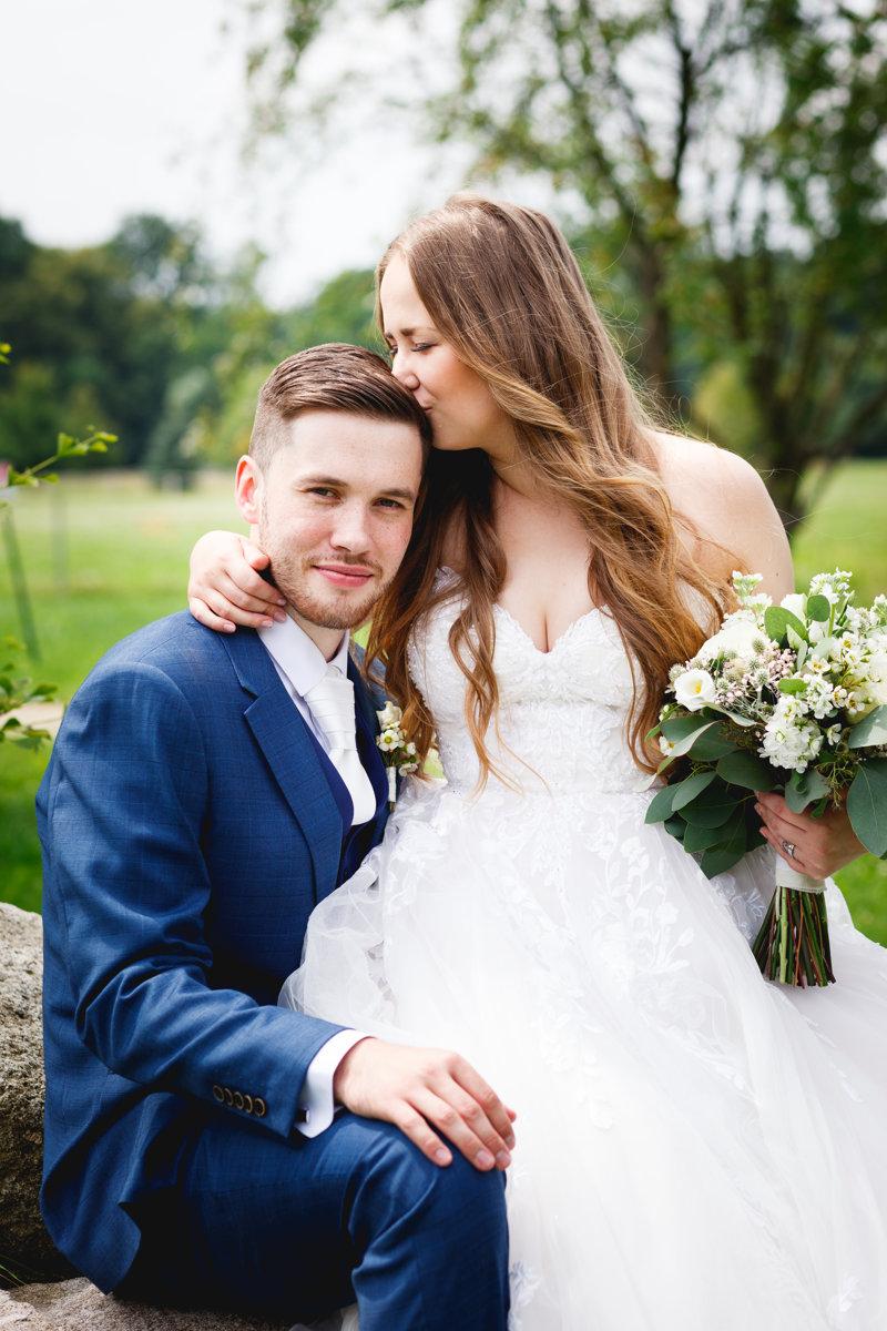 Svatební portrét, nevěsta sedí na klíně ženicha a dává mu pusu do vlasů
