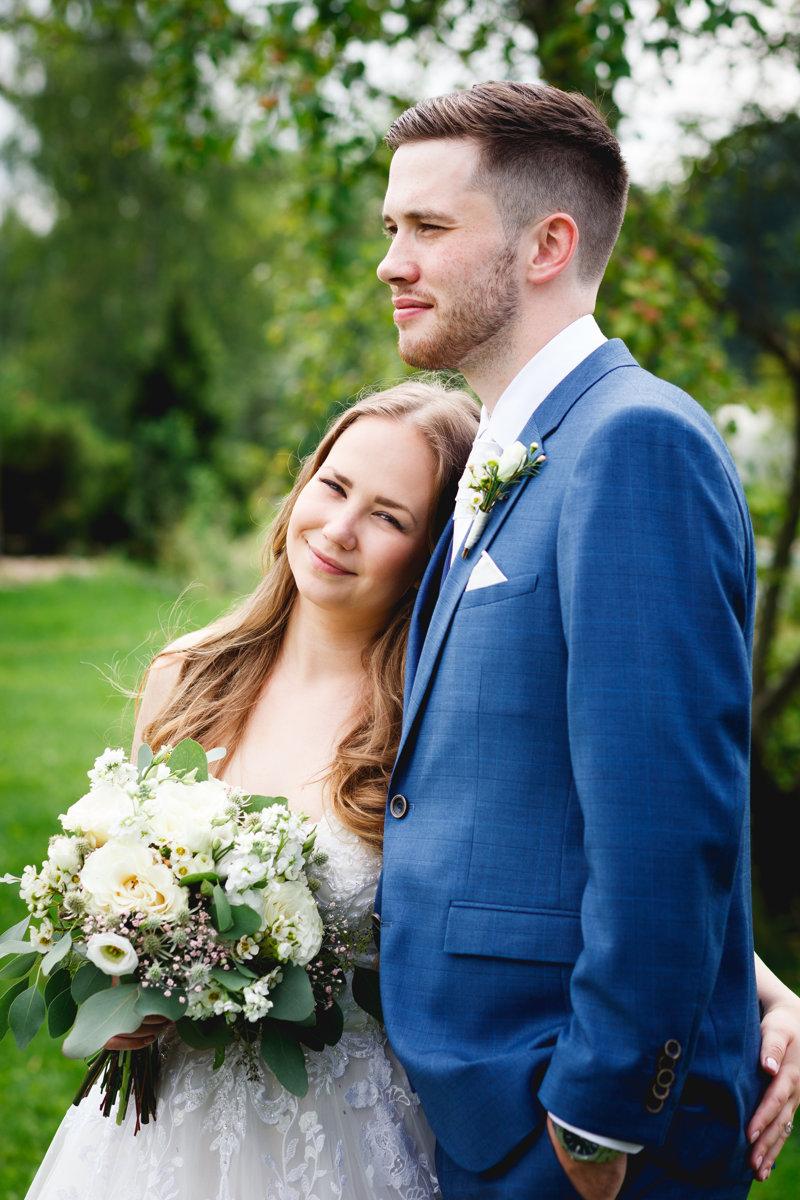 Svatební portrét, nevěsta má opřenou hlavu o ženicha zatímco kouká na fotografa