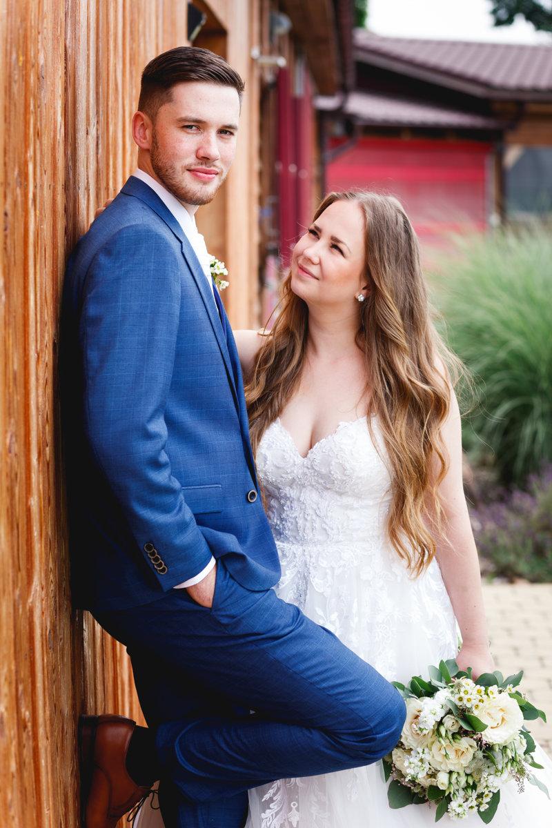 Svatební portrét, ženich stojí u zdi, nevěsta se na něho dívá