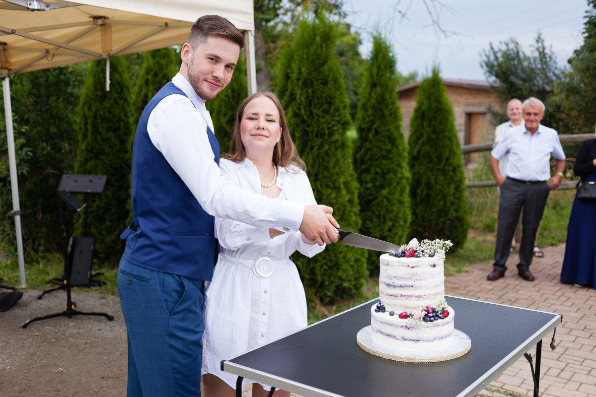 Nevěsta se ženichem koukají do foťáku a krájí dort