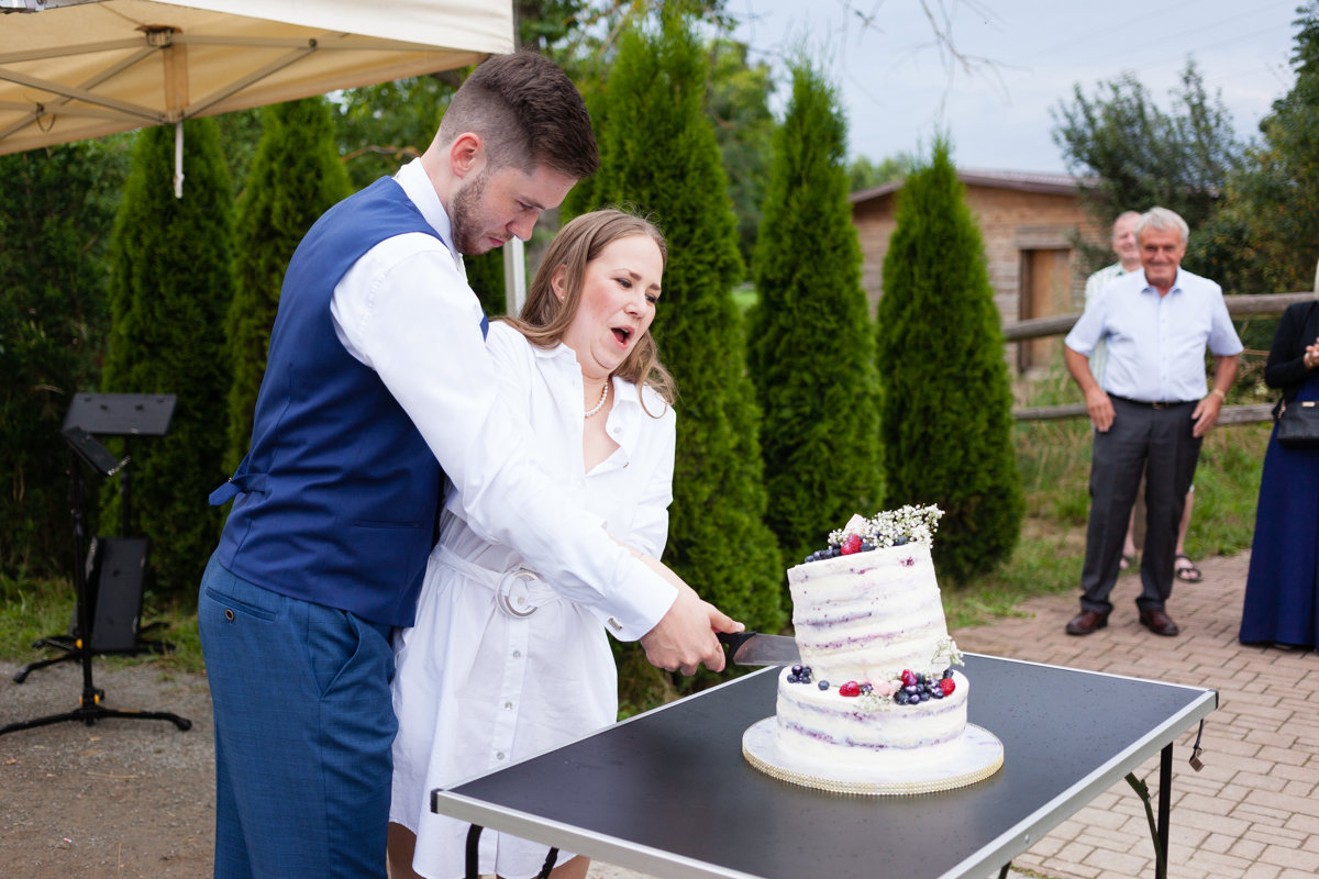Nevěsta se ženichem krájí dort, dort padá