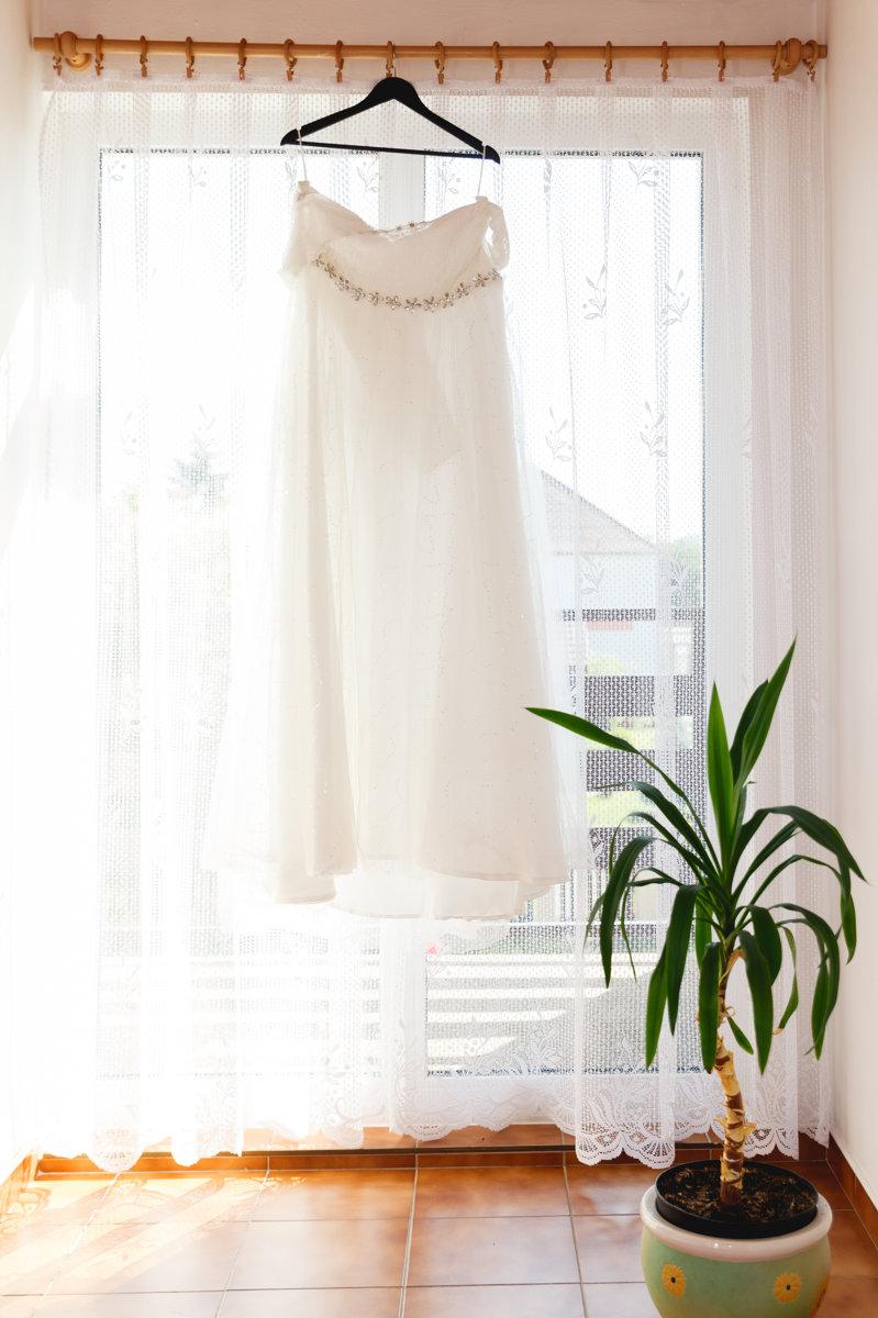 Šaty nevěsty visí na okně