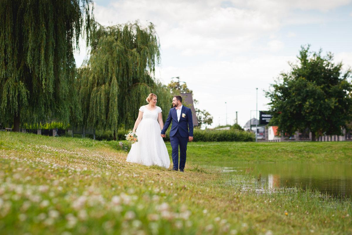 Nevěsta se ženichem se prochází kolem rybníčku, svatební portrét